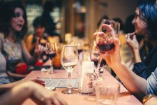 people drinking liquor and talking on dining table close up